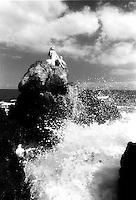 Young Hawaiian woman on rocks with the ocean splashing.
