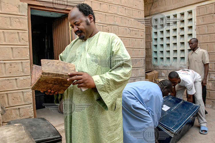 Abdel Kader Haidara looks at his family's ancient manuscripts that he is trying to preserve in his home. In the past few years, with funding from different organizations including the Ford Foundation, thousands of the manscripts are being recovered, stored, preserved and studied. Sadly, many of them have been lost or severley damaged but for those that remain it is a maginificent reminder of Africa's literary history. /Felix Features