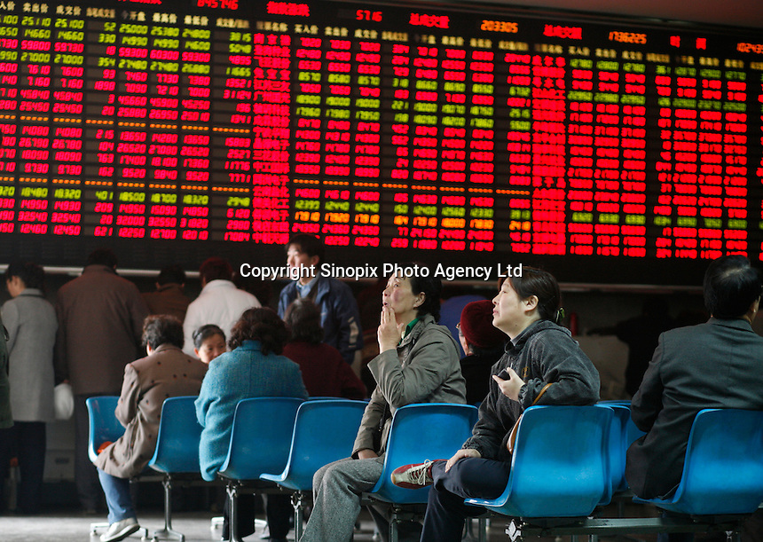 Investors sit in front of a stock trading board at a securities company in Shanghai, China.  Despite a huge sell-off here a few weeks ago that helped trigger a drop in global financial markets and continued warnings from government officials on a potential economic bubble, China's stock markets continue to soar towards record highs. .22 Mar 2007