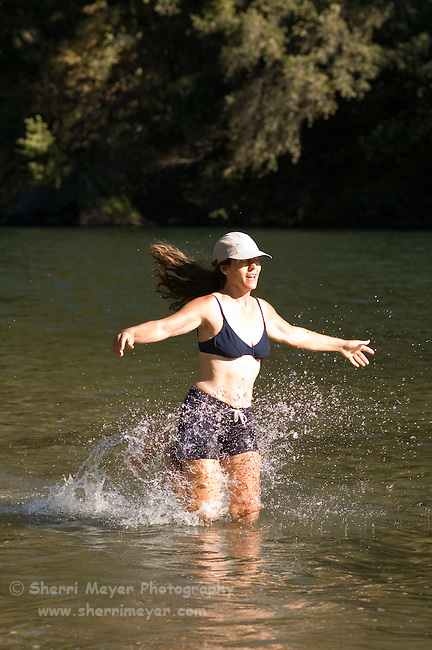 Woman playing in Lake Clementine on a hot summer day, Auburn California