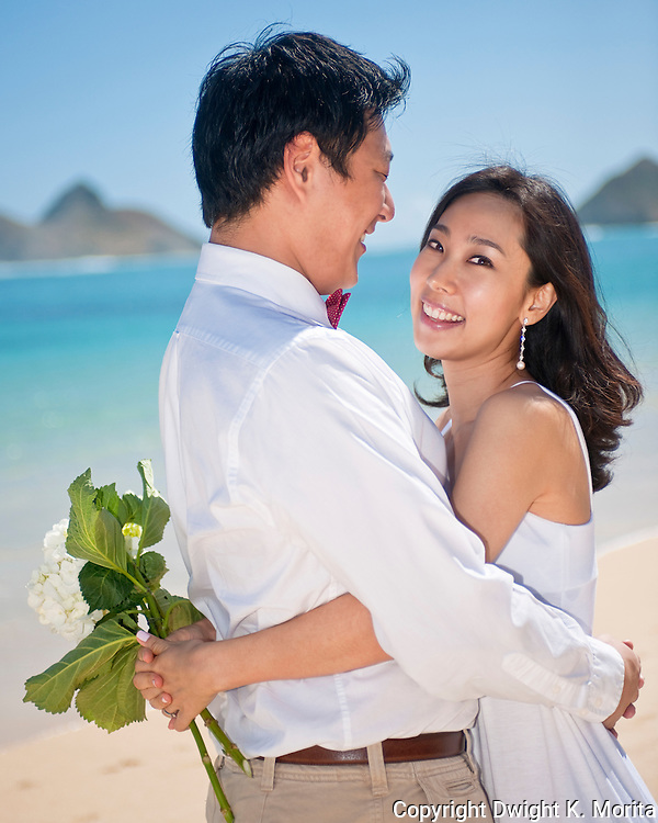 Asian couple embrace during their honeymoon on Lanikai beach, Kailua, Hawaii
