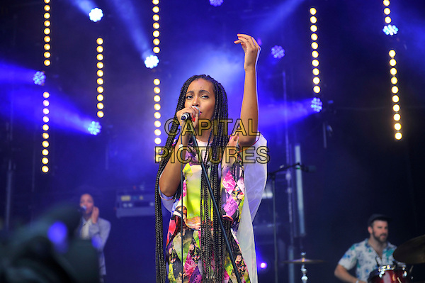 Solange (Solange Knowles) <br /> performing at Glastonbury Festival, Worthy Farm, Pilton, Somerset, <br /> England, UK, 28th June 2013.<br /> half length music gig concert gig live on stage singing long hair braids microphone hand arm raised up   pink yellow white print catsuit jumpsuit top <br /> CAP/MAR<br /> &copy; Martin Harris/Capital Pictures