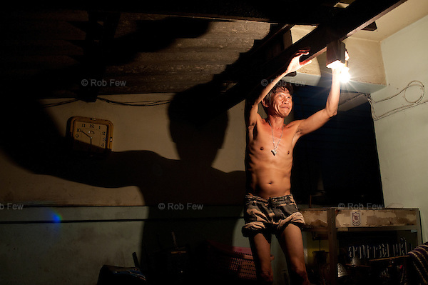 A man changes a light bulb in his flooded house, where electricity is still running on the second floor. <br /> <br /> Thailand's worst floods for 50 years finally reached the suburbs of Bangkok in October 2011. While the government dithered and argued with itself, more than 200 people died.
