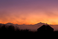 Barn silhouetted against sunrise with Cascade Mountains in background, Spencer Island, Everett, Snohomish River Estuary, Washington