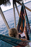 Woman lays in hammack writing, while overlooking the Caribbean Sea, Bocas Town, Bocas del Toro, Panama