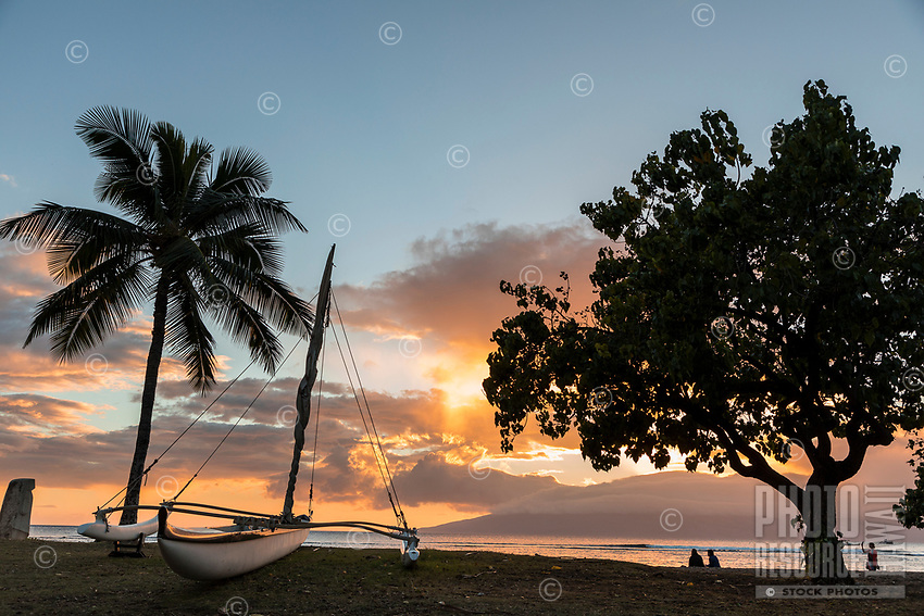 People sunset at a beach in Lahaina, with a Hawaiian sailing canoe in the foreground and Lana'i in the distance.