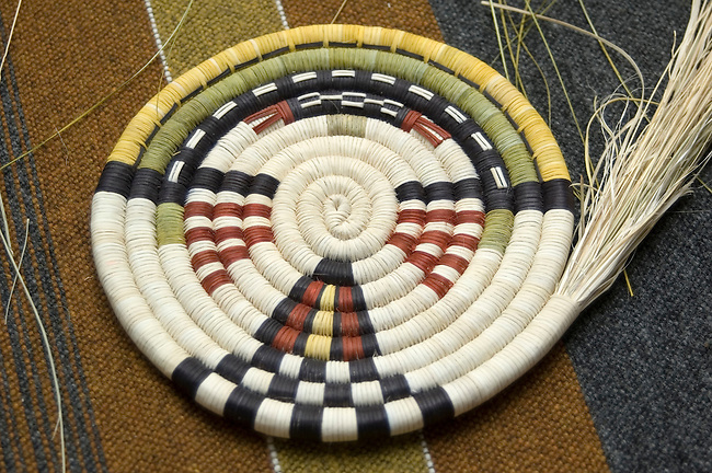 The beginning of coil weaving a traditional Hopi basket tray using natural fibers. Created by Hopi artist Griselda Saufkie, Arizona