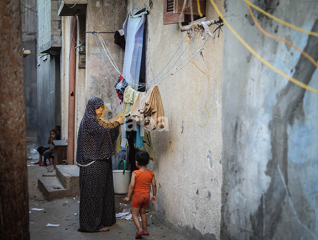 A Palestinian woman collects laundry outside her home at al-Shati refugee camp, the third largest in the Palestinian Territories, in Gaza City on October 02, 2013. Photo by Ezz Zanoun