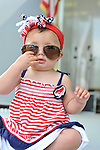 Baby girl wearing big sunglasses and red white and blue at Merrick Memorial Day Ceremony on May 28, 2012, on Long Island, New York, USA. Memorial Day ceremony reflect in the mother's sunglasses the 10-month-old baby is wearing. America's war heroes are honored on this National Holiday.