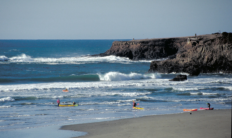 Kayakers entering the surf in Mendocino Bay with waves breaking