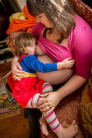 A woman  7 months pregnant breastfeeds her little girl aged nearly 3 years old on the sofa in her living room.<br /> <br /> Image from the &quot;We Do It In Public&quot; documentary photography project collection: <br />  www.breastfeedinginpublic.co.uk<br /> <br /> Dorset, England, UK<br /> 14/02/2013