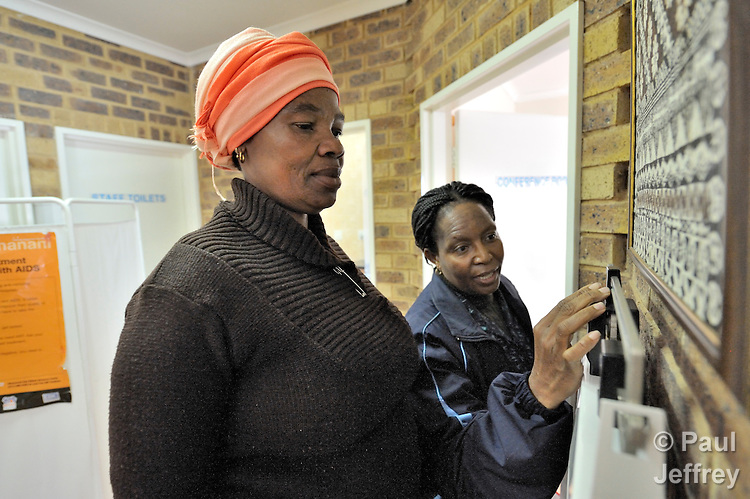 Emily Dube (right), a counselor at the St. Francis Care Centre in Johannesburg, South Africa, weighs Nompumelelo Ngebeza as part of a general health assessment before testing her for HIV. The centre is a project of the Roman Catholic Archdiocese of Johannesburg, and is supported by Catholic Relief Services, a member of the Ecumenical Advocacy Alliance.