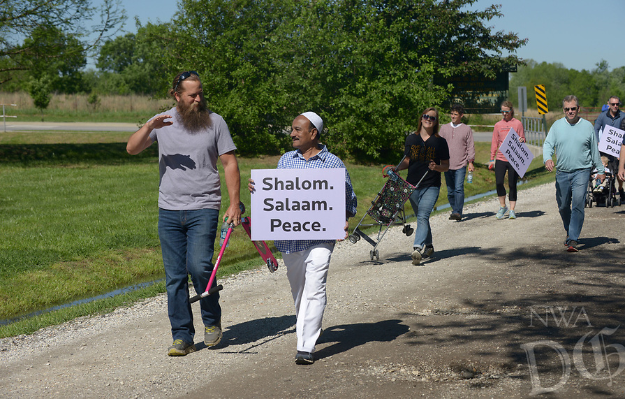 NWA Democrat-Gazette/BEN GOFF @NWABENGOFF<br /> Bryan Smith (left), a member of Waterway Christian Church, and Abdul Rahim, a member of the Bentonville Islamic Center, chat as they walk Sunday, April 23, 2017, as participants in the Abraham Peace Walk from Waterway Christian Church to the Bentonville Islamic Center make a rest stop at Lake Bentonville. Members of Waterway Christian Church, First Christian Church of Bentonville, Congregation Etz Chaim and the Bentonville Islamic Center walked together in a show of peace between Christianity, Judaism and Islam, which all trace their roots to the biblical patriarch Abraham.