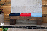 Bold colored cushions on simple wooden bench against garden wall on patio