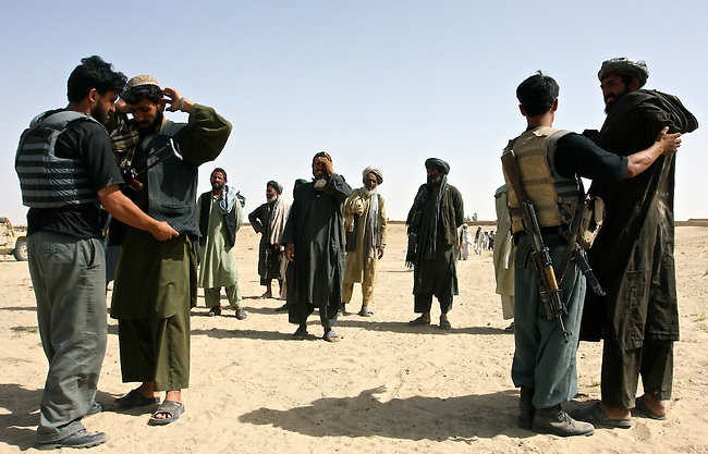 Afghan police officers search local men before a meeting between village elders and NATO soldiers in Osman Kheyl, Maiwand district, Afghanistan. The elders were urged not to support the Taliban and cooperate with security forces. Taliban attacks have risen sharply across southern Afghanistan in the last two years, and U.S. and other NATO countries are sending more troops to the region. Aug. 7, 2008. DREW BROWN/STARS AND STRIPES