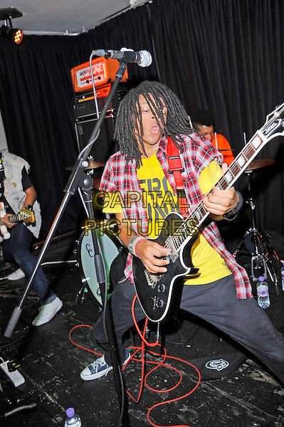 Dee Radke of Radkey <br /> performing in concert, The Blackeart, Camden, London, England. <br /> 17th October 2013<br /> on stage in concert live gig performance performing music full length red check shirt yellow top guitar  jeans denim<br /> CAP/MAR<br /> &copy; Martin Harris/Capital Pictures