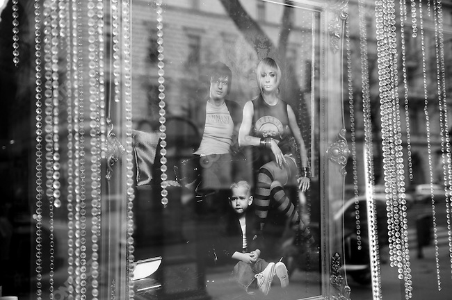 In the window of a hairdressing salon on Andrassy Road a photograph of a stylised family of three advertised the salon's services. Budapest, Hungary, March 23, 2008