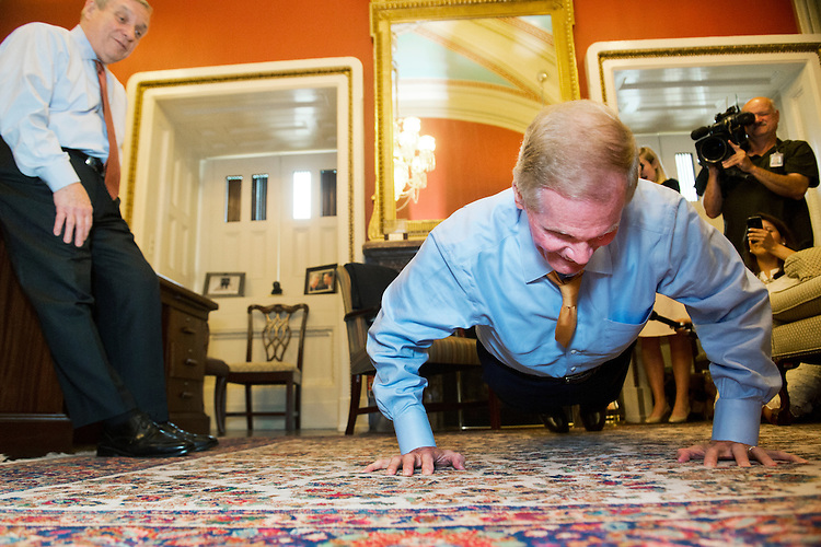 UNITED STATES - JUNE 17: Sen. Bill Nelson, D-Fla., does forty-six pushups as Senate Minority Whip Richard Durbin, D-Ill., looks on, as part of a bet payoff on the Stanley Cup championship series between the Chicago Blackhawks and the Tampa Bay Lightning, June 17, 2014. The Blackhawks won the series 4-2. Forty-six was double the goals scored in the series. (Photo By Tom Williams/CQ Roll Call)