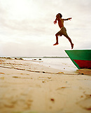 PANAMA, Bocas del Toro, boy jumping of a fishing boat onto the beach