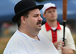 """The arbiter - the precursor to the modern baseball umpire - watches a recent vintage base ball game on August 4, 2012 at the Swansea Moose Lodge fields between the Belleville Stags and the St. Louis Unions.  He is portrayed by """"Judge"""" David P. Showmaker, who is wearing authentic period attire.  The derby is an original from the late 19th century, and was bought on eBay.  The other clothes were bought from a shop that specializes in historical clothing.  The teams played by rules of the game as they were in the late 19th century -- when there were no umpires, only a lone arbiter to make judgement calls."""