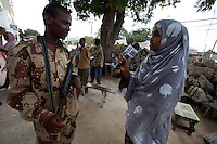 Ifrah Hassan Mohammad, 19 years old, TV reporter for GBC ( Global Broadcast Corporation )  interviews a militia man loyal to the TFG ( transitional federal government )  in Mogadishu, Somalia on Monday January 01 2007..Only a few days after the fall of the United Islamic Courts in Mogadishu, Ethiopian and Transitional Federal Government troops are patrolling the city and securing strategic locations..The people in Mogadishu appear confused and doubtful on t