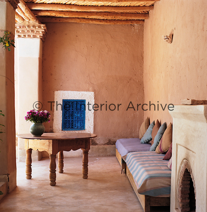 Wooden banquettes line an adobe wall in the shelter of a terrace that overlooks the inner courtyard