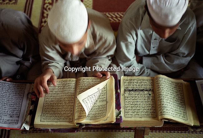 "Unidentified young boys read the Koran at a Madrasa ""Qur'an school"" on September 24, 2001 in Rawalpindi 10 miles from Islamabad, Pakistan. The students, age 5-18 come from all over the country to live and study at the school. Many of these schools are recruiting grounds for the Taliban movement in Afghanistan, who are enforcing a strict law on the people of Afghanistan. (Photo by: Per-Anders Pettersson)...."
