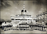 BNPS.co.uk (01202 558833)<br /> Pic:    CanterburyAuctionGalleries/BNPS<br /> <br /> The ship's crew of 1,345 pose for the obligatory company photo in Le Havre harbour.<br /> <br /> Remarkable photos of the iconic ocean liner SS Normandie which was like a 'floating palace' have come to light over 80 years later.<br /> <br /> The giant 1,000ft long French passenger ship was the largest of her type in the world and won the coveted 'Blue Riband' for the fastest crossing of the Atlantic.<br /> <br /> English photographer Percy Byron's photos show the liner's luxurious 'Art Deco' interior with its chandeliers and pillars of Lalique glass.<br /> <br /> The vessel, which launched in 1935, even boasted its own swimming pool and a gym where young women can be seen doing aerobics while a man in a suit trains with a punch bag.