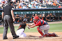 Miami Marlins Jordany Valdespin (1) is tagged out while sliding into home by catcher Dan Butler (48) for the Washington Nationals during a spring training game against the Miami Marlins at the Roger Dean Complex in Jupiter, Florida on March 10, 2015. Miami defeated Washington 2-1. (Stacy Jo Grant/Four Seam Images)