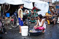 Monic fait sa lessive à l'exérieur de l'astrodrôme où se trouve un point d'eau. Elle est accompagnée de sa nièce. Tacloban, Novembre 2013. VIRGINIE NGUYEN HOANG