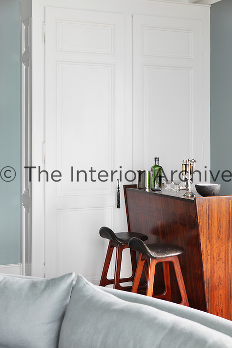 Detail of a retro wooden bar with a pair of stools in one corner of the living room