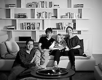 Portrait of the Holden and Amelia Shannon and their children sitting on a sofa in their living room