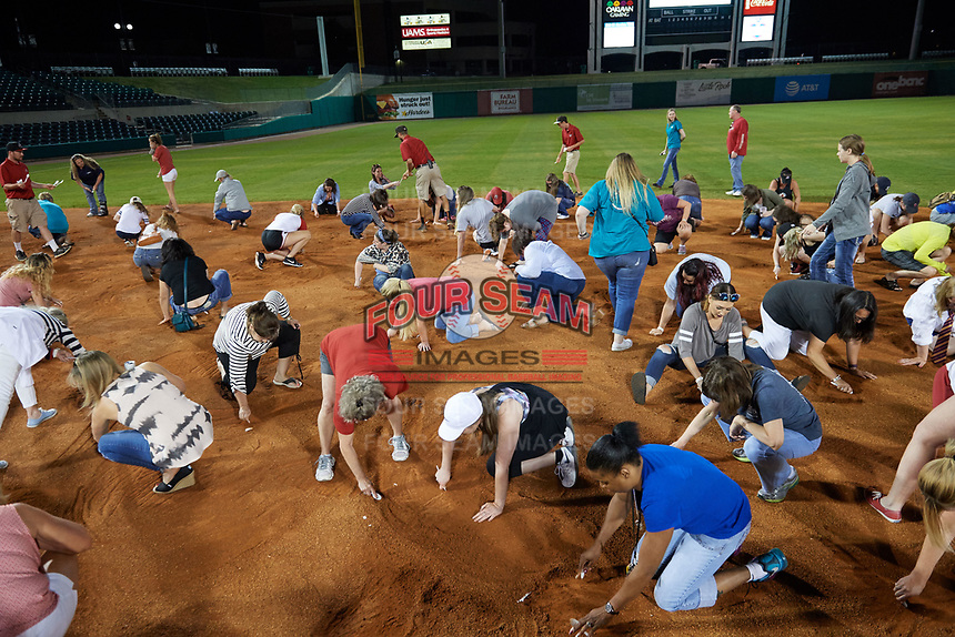 "Arkansas Travelers female fans search the infield for a buried diamond ring during the teams annual ""Diamond Dig"", presented by Lee Ann's Fine Jewelry, after a game against the Midland RockHounds on May 25, 2017 at Dickey-Stephens Park in Little Rock, Arkansas.  Midland defeated Arkansas 8-1.  (Mike Janes/Four Seam Images)"