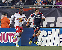 New England Revolution midfielder Kelyn Rowe (11) brings the ball forward as New York Red Bulls midfielder Lloyd Sam (10) closes. In a Major League Soccer (MLS) match, the New England Revolution (blue) tied New York Red Bulls (white), 1-1, at Gillette Stadium on May 11, 2013.