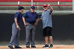 RALEIGH, NC - MARCH 29: NC State head coach Shawn Rychcik (right) talks to third base umpire David Brewer (center) and first base umpire Alex Leap (left). The North Carolina State University Wolfpack hosted the Liberty University Flames on March 29, 2017, at Dail Softball Stadium in Raleigh, NC in a Division I College Softball game. Liberty won the game 5-3.