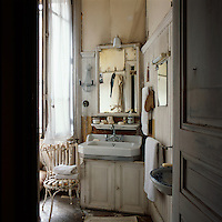 A view into a bathroom with a faded air. A mirror is set above a basin placed on a cupboard unit.