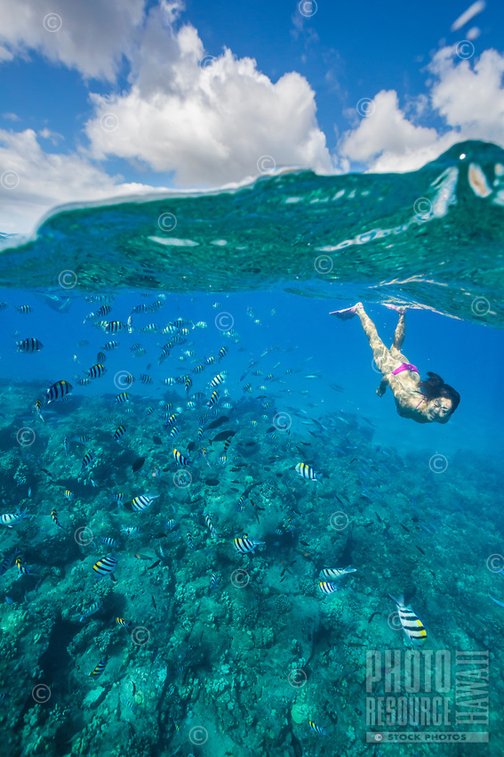 A woman swimming above a reef, Electric Beach, West O'ahu