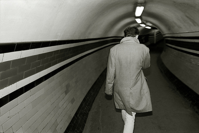 A young man, seen from behind, hurries along a subway tunnel in the London Underground. England 2008.