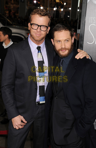 "McG (Joseph McGinty Nichol) & Tom Hardy.""This Means War"" Los Angeles Premiere held at Grauman's Chinese Theatre, Hollywood, California, USA..February 8th, 2012.half length black suit glasses purple shirt beard facial hair .CAP/ROT/TM.©Tony Michaels/Roth Stock/Capital Pictures"