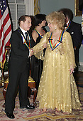 Singer Paul Simon with actress Elizabeth Taylor after a group photo of the 2002 Kennedy Center Honorees at the United States Department of State in Washington, D.C. on Saturday, December 7, 2002.  They are honored for their lifetime contributions to American culture through the performing arts..Credit: Robert Trippett - Pool via CNP