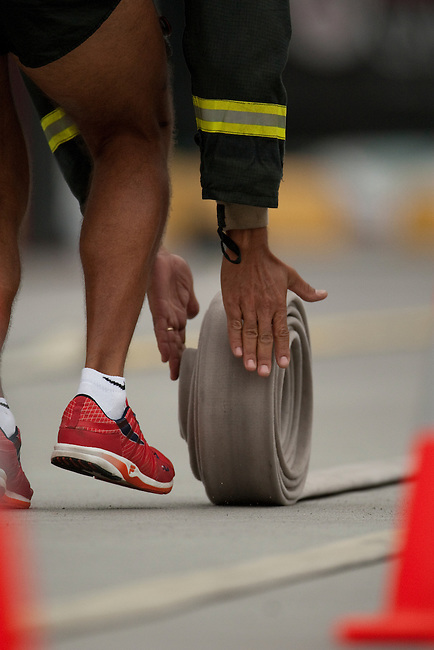 Ultimate Firefighter Competition, World Police and Fire Games, Vancouver, Aug 6th 2009.  A competitor in the Hose Task stage of the competition  rolls up one of two 50-foot lengths of 2 ½-inch fire hose. After rolling them up, he will pick them up and run to the finish line.  Photo by Gus Curtis