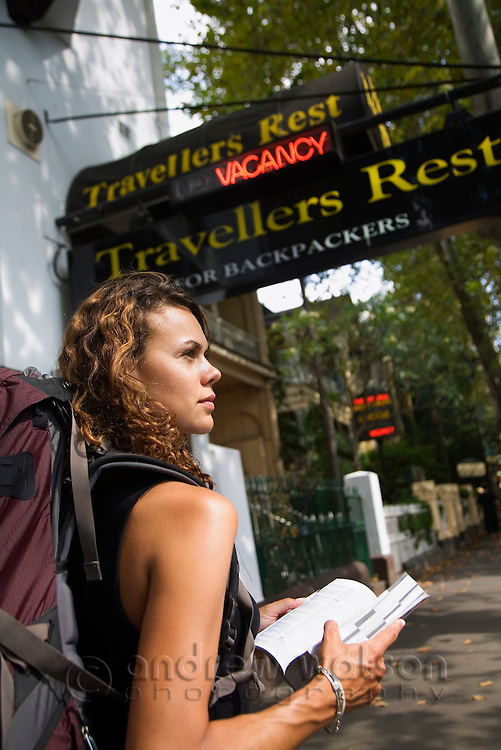 A backpacker checks her guidebook for places to stay.  Kings Cross, Sydney, New South Wales, AUSTRALIA.