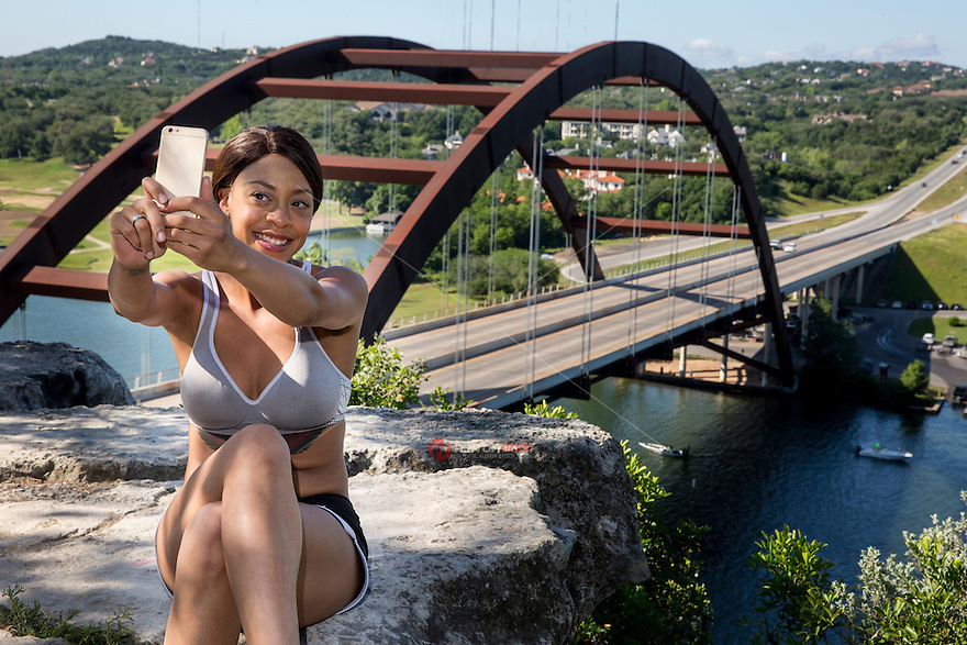 Beautiful African-American young woman takes selfie on the 360 Bridge overlook cliff on Lake Austin, Texas.