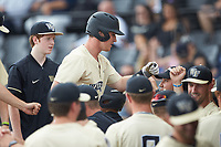 Chris Lanzilli (24) of the Wake Forest Demon Deacons is greeted by his teammates after scoring a run against the Virginia Cavaliers at David F. Couch Ballpark on May 19, 2018 in  Winston-Salem, North Carolina.  The Demon Deacons defeated the Cavaliers 18-12.  (Brian Westerholt/Four Seam Images)