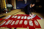 Kyoto, Japan..Mineko Iwasaki at home organizing sashes she once wore as Kyoto's most famous geisha...All photographs ©2003 Stuart Isett.All rights reserved.