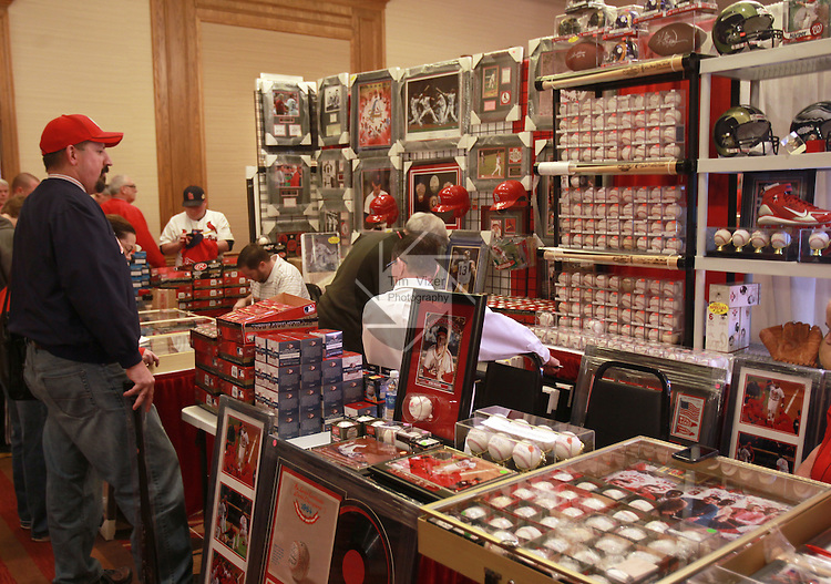 A St. Louis Cardinals fan looks over baseball memorabilia and other merchandise for sale at the 17th Annual Cardinals Winter Warm-Up at the Hyatt Regency at the Arch in downtown St. Louis. The annual event raises money for the Cardinals Care program, which is the team's community foundation supporting kids.  Since its start in 1997 - and thanks to Cardinals fans, players, staff, volunteers, and sponsors - Cardinals Care has distributed more than $18 million to area organizations.