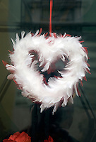 Detail of a heart made out of feathers hanging in a window