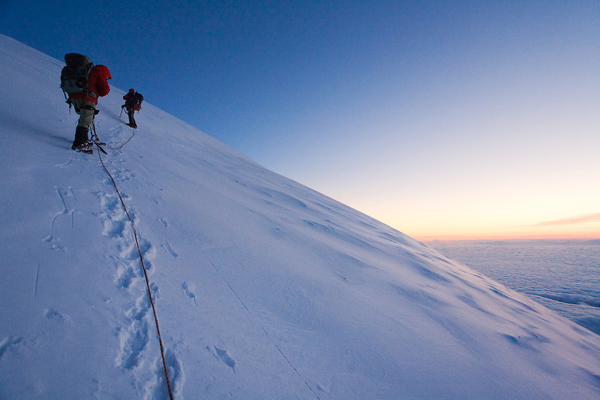 """RAINIER DAWN"" -- Roped mountain climbers ascend the upper slopes of Washington State's Mount Rainier. During a break at nearly 14,000 feet, the climbers enjoy a beautiful sunrise."