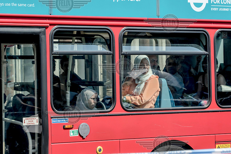 Women watch from a bus as a vigil for victims of the Finsbury Park mosque terrorist attack takes place. On 19 June 2017 a van, allegedly by driven by Darren Osborne who is currently in custody, was deliberately driven into worshippers leaving the mosque, killing one man and injuring 10 others.