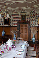 The colourful wallpaper in the gothic dining room is matched by the table laid with colourful china and pink glassware